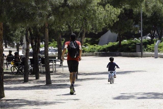 Un hombre hace deporte con un niño en bicicleta por Madrid Río.