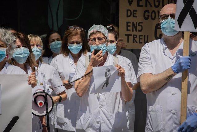 Una sanitaria habla por un megáfono junto a otros compañeros de profesión a las puertas del Hospital Clínic de Barcelona donde sostienen pancartas y crespones negros para reivindicar contratos dignos y más personal. En Barcelona, a 27 de mayo de 2020.