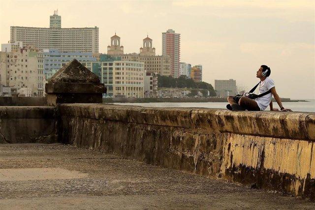 Un joven escucha música en el Malecón de La Habana