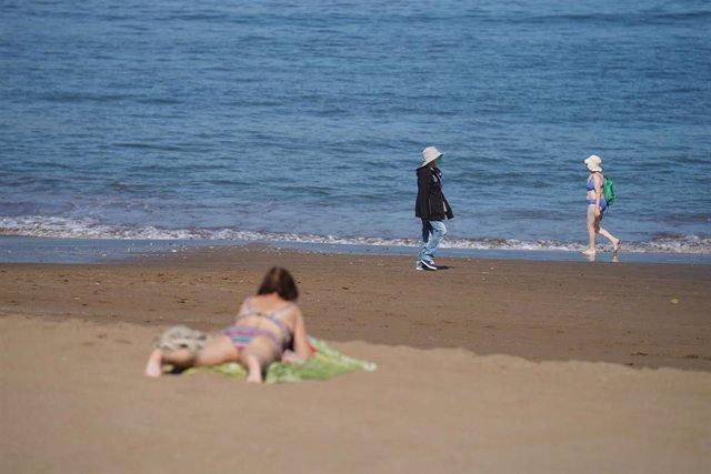 Varias personas pasean y toman el sol en la Playa de Ereaga en Getxo