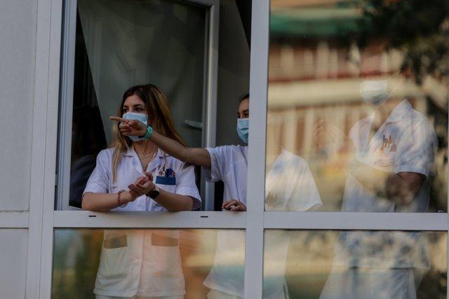 Sanitarios aplauden desde una ventana de del Hospital Fundación Jiménez Díaz cuando en la Fase 1 de la desescalada continúan los aplausos en homenaje a los profesionales sanitarios