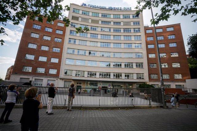 Sanitarios y varios transeúntes aplauden en la puerta del Hospital Fundación Jiménez Díaz de Madrid