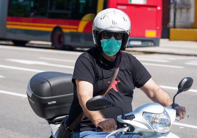 Un motorista con mascarilla  en el  primer día del uso obligatorio de mascarillas por el Covid-19. Sevilla a 21 de mayo del 2020