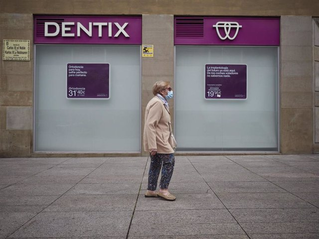Una mujer paseas enfrente de una clínica Dentix el día en el que está permitida la apertura de locales y establecimientos minoristas con independencia de su superficie útil de exposición y venta. En Pamplona, Navarra (España), a 25 de mayo de 2020.