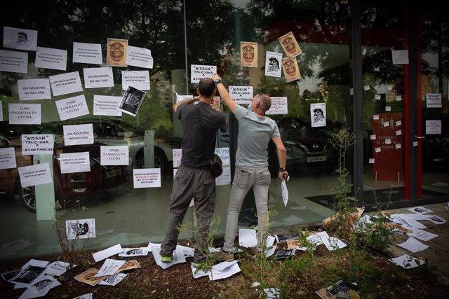 Varios trabajadores de Nissan cuelgan carteles como signo de protesta en el corte que han realizado en la Gran Vía de L'Hospital (Barcelona), cerca del concesionario de Nissan Motor Llansà, uno de los cuatro concesionarios donde los comités de empresa del