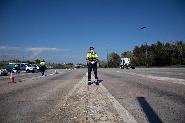 Varios agentes de los Mossos d'Esquadra protegidos con mascarillas en un control en el peaje de La Roca del Vallès durante un Jueves Santo atípico en el que prosigue el estado de alarma decretado por el Gobierno para la lucha contra el coronavirus, en La