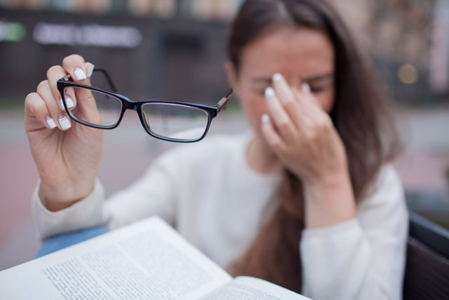 Closeup portrait of attractive female with eyeglasses in hand. Poor young girl has issues with vision. She rubs her nose and eyes out of fatigue. A student tired to study and read books