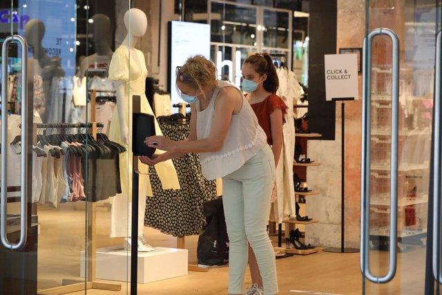 Dos mujeres con mascarilla en el interior de una tienda de ropa en el primer día de la fase 1 en Madrid, en la que se permite reapertura de locales y establecimientos minoristas