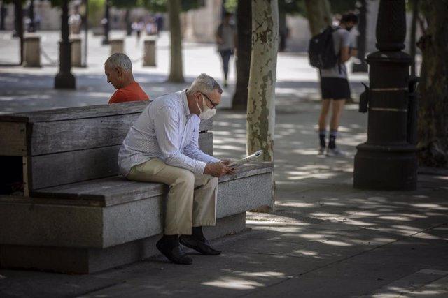 Un hombre con mascarilla lee el periódico sentado en un parque.