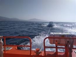 Lancha semihundida remolcada por Salvamento Marítimo