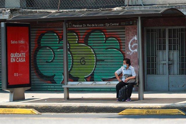 Una mujer con mascarilla espera en una parada de autobús en Ciudad de México.