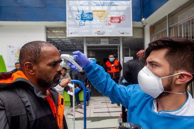 Médico ecuatoriano toma  la temperatura a un hombre en la frontera con Colombia.
