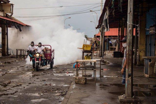 Dos hombres desinfectan el Mercado Las Pulgas, foco de infección de coronavirus en Maracaibo, Venezuela.