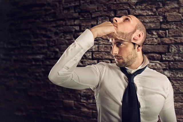 Un hombre quitándose una máscara de sí mismo. Síndrome de Capgras.