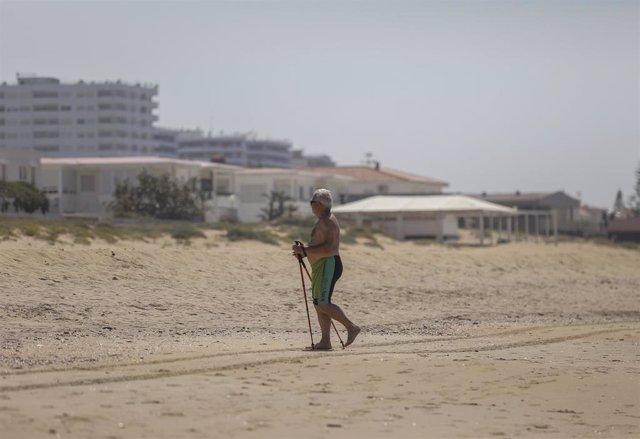Una persona en la playa de Punta Umbría, abierta para el paseo y la práctica deportiva como único uso permitido, durante la segunda semana de la Fase 1. En Punta Umbría (Huelva, Andalucía, España), a 21 de mayo de 2020.