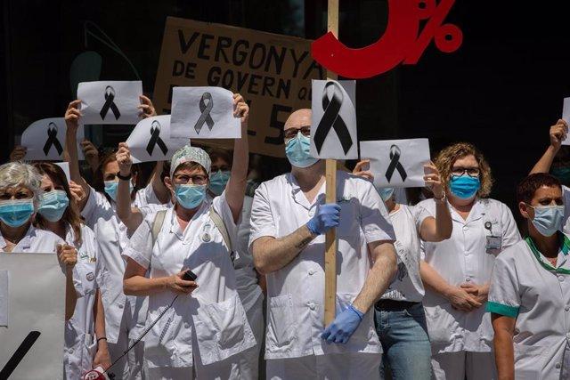 Trabajadores sanitarios protegidos con mascarilla se reúnen a las puertas del Hospital Clínic de Barcelona con pancartas y crespones negros para reivindicar contratos dignos y más personal, así como recordar a los fallecidos por la crisis del Covid-19.