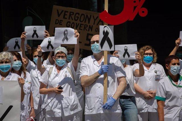 Treballadors sanitaris protegits amb mascarilla es reuneixen a les portes de l'Hospital Clínic de Barcelona amb pancartes i crespons negres per reivindicar contractes dignes i més personal, així com recordar als morts per la crisi del Covid-19.