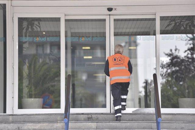 Una sanitaria entra por la puerta del Hospital San Jorge en Huesca