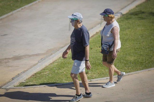 Dos personas con ropa veraniega y gorra pasean por el parque del Alamillo. En Sevilla (Andalucía, España), a 21 de mayo de 2020.