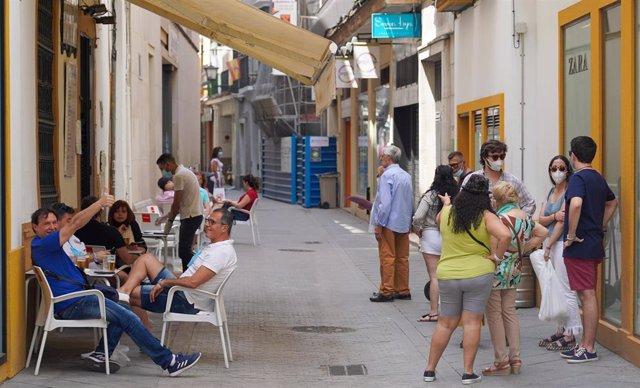 En un bar céntrico de Sevilla, los clientes ocupan todas las mesas de la terraza  y otros esperan una cola para poder consumir en el inicio de la Fase 2