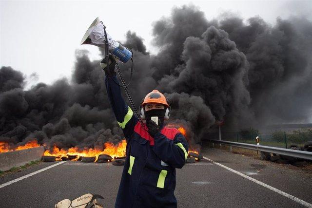 Un participante de la manifestación del comité de empresa de Alcoa habla por un megáfono junto a la quema de unos neumáticos tras el anuncio hace tres días del despido colectivo a 31 de mayo de 2020