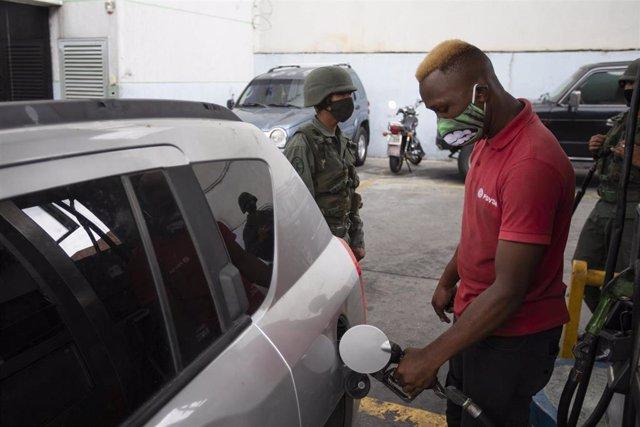 Un hombre con mascarilla echa gasolina de Caracas
