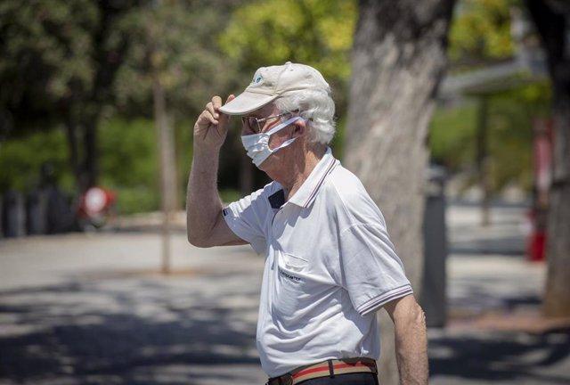 """Un hombre con mascarilla y gafas de sol se coloca una gorra durante un """"episodio de altas temperaturas"""". Según la calificación de la  Agencia Estatal de Meteorología (AEMET). En Sevilla,(Andalucía, España), a 22 de mayo de 2020."""