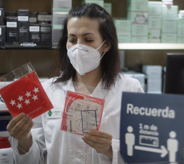 Una farmacéutica muestra una mascarilla en la Farmacia CEA, una de las 2.882 farmacias madrileñas