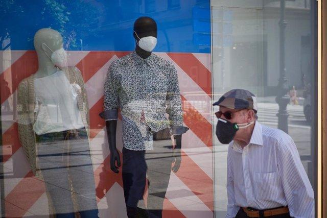Un hombre protegido con mascarilla pasea por las calles de Pamplona