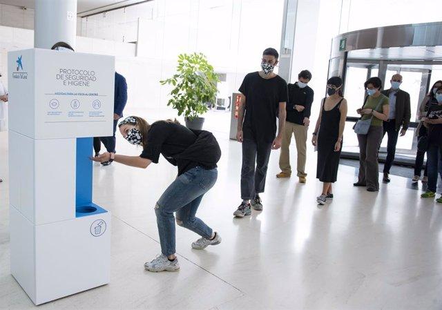 Visitants del Caixaforum de Barcelona usen un dispensador de gel abans d'accedir a les sales d'exposició.
