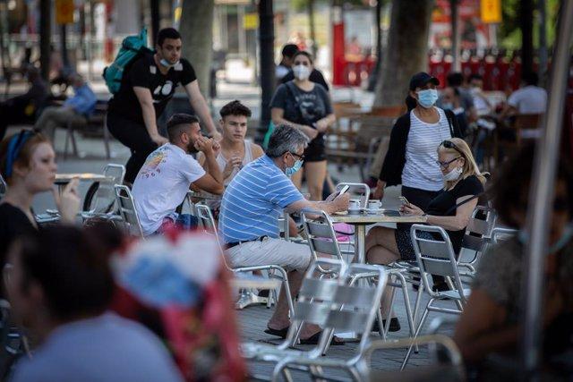 Diverses persones gaudeixen en la terrassa d'un bar, durant el segon dia de la Fase 1 a Barcelona, Catalunya (Espanya) a 26 de maig de 2020.
