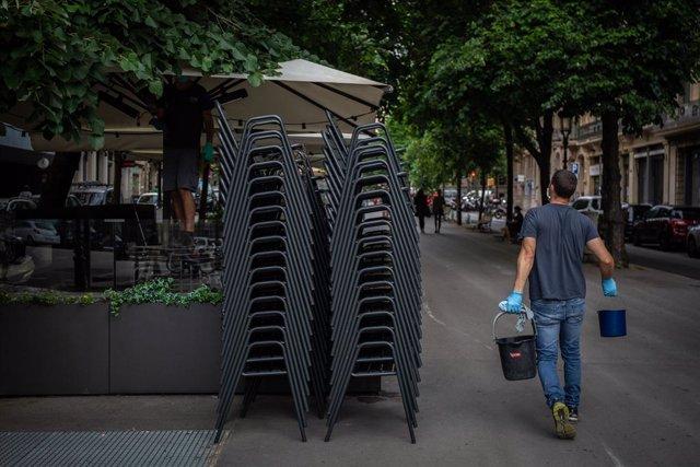 Un home passa al costat de la terrassa d'un bar durant el primer dia de la Fase 1. A Barcelona, Catalunya (Espanya), a 25 de maig de 2020.