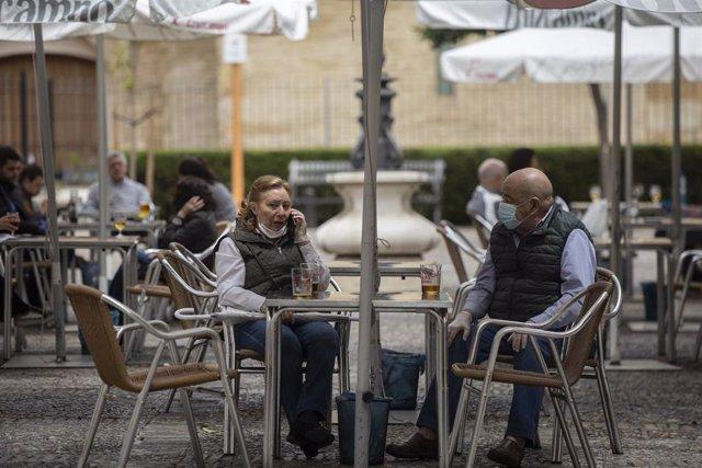 Personas consumiendo en los veladores de un bar abierto