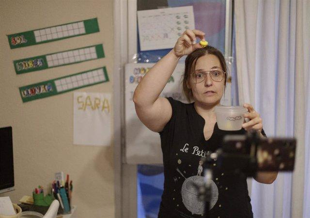 Una profesora de Educación Infantil graba con su móvil una clase para sus alumnos durante el confinamiento.