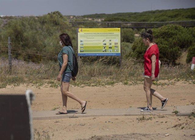 Dos personas caminan hacia la playa de Punta Umbría, abierta para el paseo y la práctica deportiva como único uso permitido, durante la segunda semana de la Fase 1. En Punta Umbría (Huelva, Andalucía, España), a 21 de mayo de 2020.