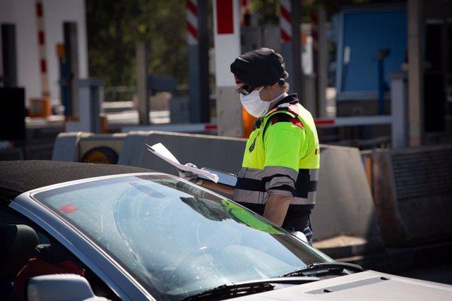 Un agent dels Mossos d'Esquadra protegit amb una mascarilla en un control en el peatge de La Roca del Vallès