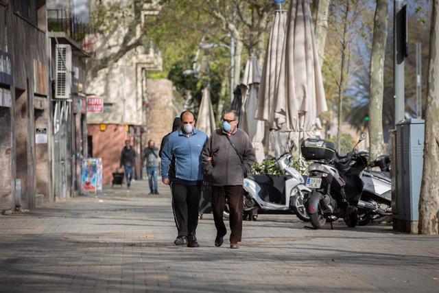 Dos homes protegits amb mascarillas caminen per un carrer durant el novè dia laborable des que es va decretar l'estat d'alarma al país a conseqüència del coronavirus, a Barcelona/Catalunya (Espanya) a 26 de març de 2020.