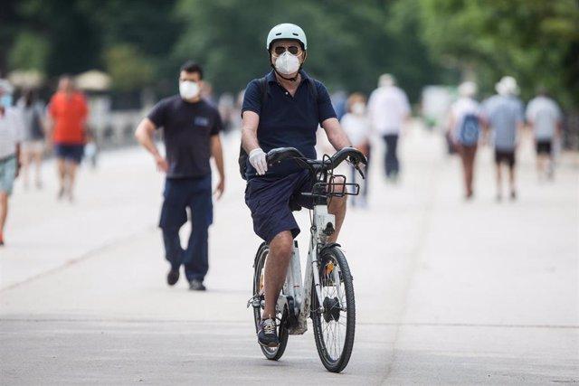 Un hombre protegido con mascarilla y guantes monta en una bicicleta