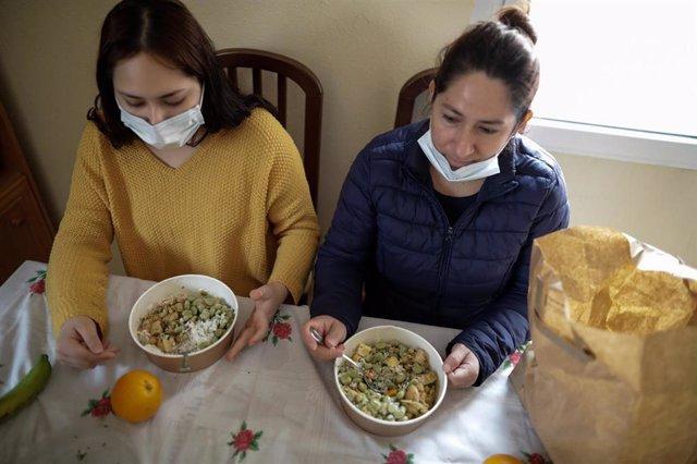 Dos mujeres durante la comida en su casa del barrio madrileño de Carabanchel comen el menú de la ONG del chef José Andrés, que reparte en Madrid a las familias más necesitadas durante el estado de alarma provocado por el coronavirus, en Madrid (España) a