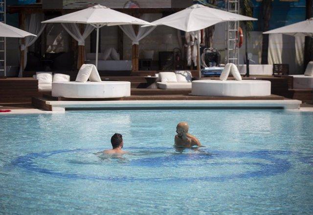 Dos personas se bañan en la piscina recreativa del Club Ocean, abierto al público durante la Fase 2, en Sevilla