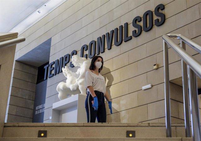 Una mujer protegida con guantes y mascarilla a la entrada de una exposición en el Museo Institut Valencià d'Art Modern (IVAM)