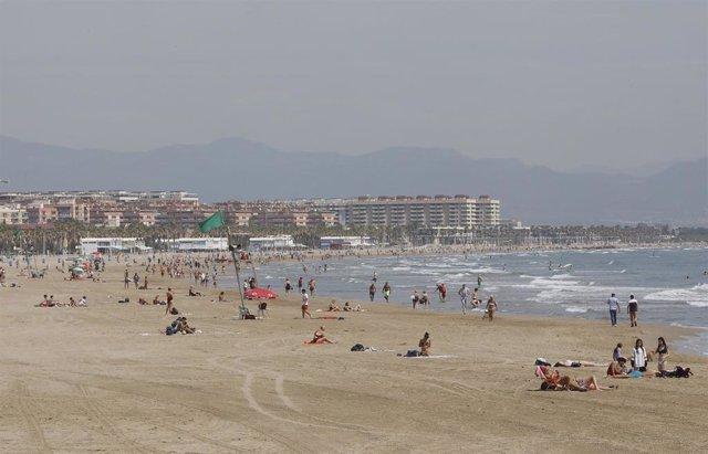Bañistas en la Playa de la Malvarrosa, con bandera verde durante el primer día de la Fase 2, cuando se puede acceder a las playas de la misma provincia, isla o unidad territorial de referencia establecida en el plan de desescalada