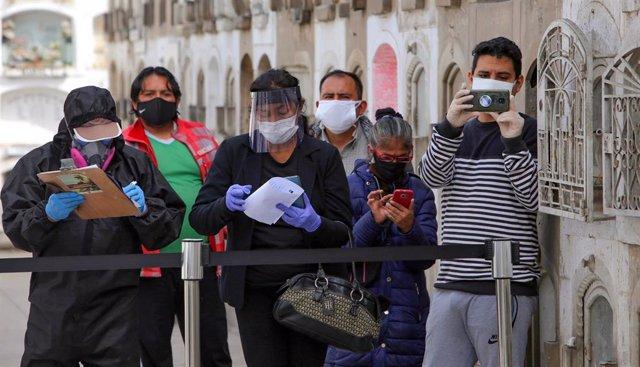 Un grupo de personas inmortaliza  graba el funeral ed uno de sus familiares en el cementerio de El Ángel, en Lima, Perú, en medio de la crisis sanitaria provocada por la pandemia de la COVID-19.