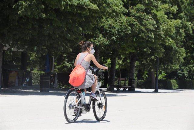 Una joven se desplaza en bicicleta por el Parque de El Retiro durante el cuarto día de la Fase 1 en Madrid, que supuso la apertura de los grandes parques de Madrid, que permanecían cerrados para evitar aglomeraciones, y que se suman a los recintos de dist