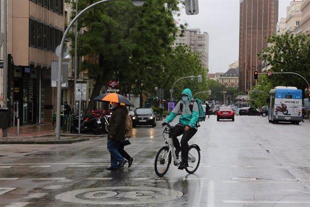 Un ciclista en Madrid en un día de lluvia
