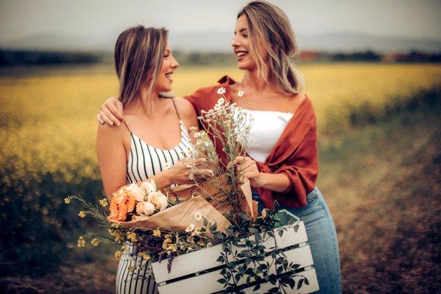 Gemelas en el campo recogiendo flores.