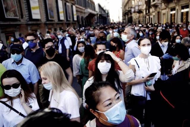 Ciudadanos con mascarillas esperando a la pasada de un avión de la Fuerza Aérea italiana durante la celebración del Día de la República
