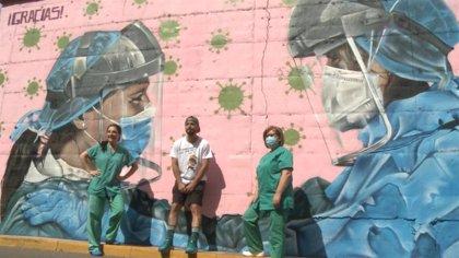 Un artista urbano realiza un graffiti en un muro del Hospital Materno Infantil de Badajoz en homenaje a los sanitarios