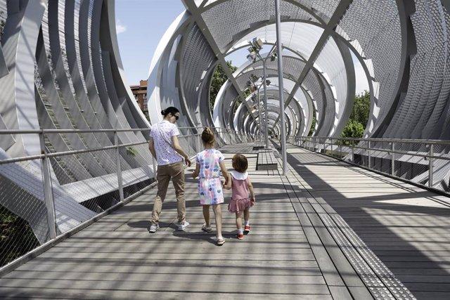 Una mujer con sus hijos en el Puente Monumental de Arganzuela en Madrid Río. En Madrid (España), a 25 de mayo de 2020.