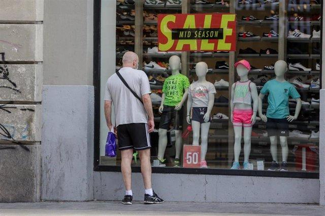 Un hombre mira el escaparate de una tienda Décimas